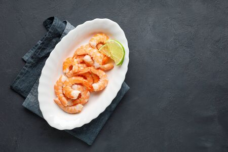 Seafood. Boiled shrimp in a plate on a black background. Top view with copy space.