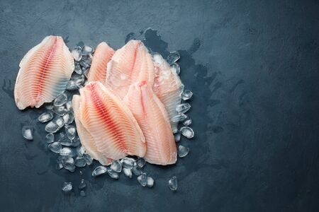 Fresh fish fillet of sea bass in ice on a dark slate background. Top view with copy space.