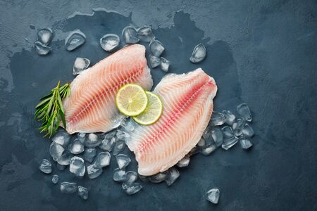 Fresh fish fillet of sea bass in ice on a dark slate background. Top view. Reklamní fotografie
