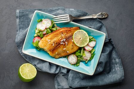Grilled fish sea bass with fresh herbs, radish and lime in a rectangular blue plate. Dark background.
