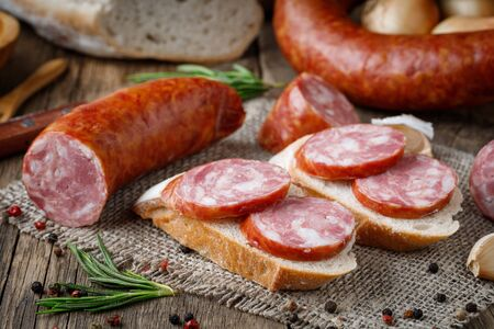 Sandwich with smoked sausage. Dry-cured sausage, bread and spices on a wooden table.