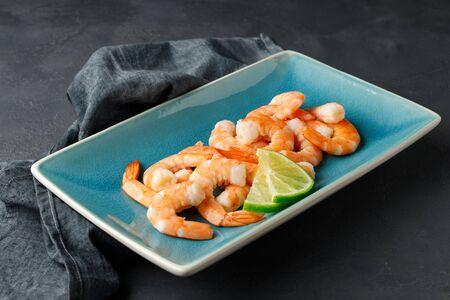 Seafood. Boiled shrimp in a plate on a black background. Reklamní fotografie