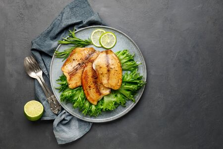 Grilled fish sea bass fillet with green lettuce in a plate on a black stone background. Above view.