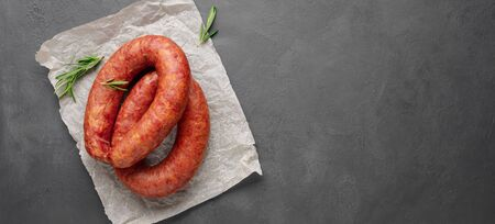 Smoked sausage with rosemary on a gray slate background. Copy space for text.