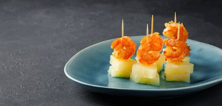 Canapes with shrimp and pineapple. Party food. Dark background. Reklamní fotografie