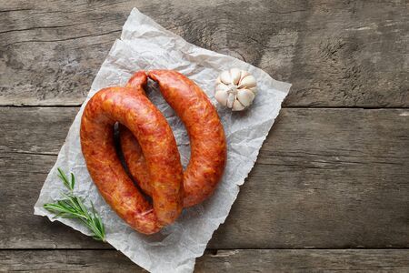 Smoked sausage with rosemary and spices on a wooden table. Top view. Flat lay. Copy space for text.