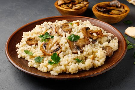Traditional italian cuisine meal - vegetarian risotto with mushrooms. Black stone backround. Reklamní fotografie