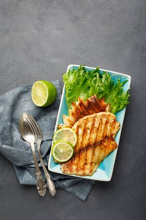 Grilled fish with fresh herbs and lime in a rectangular blue plate. Dark background.