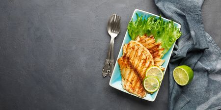 Grilled fish with fresh herbs and lime in a rectangular blue plate. Dark background. Top view with copy space.