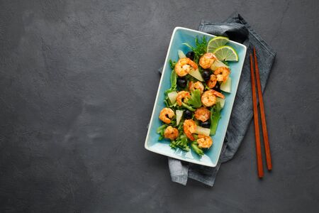 Salad with shrimp, pineapple and fresh herbs in a blue plate on a black background. Healthy food. Top view. Reklamní fotografie