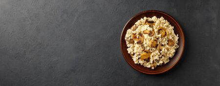 Traditional italian cuisine meal - vegetarian risotto with mushrooms. Black stone backround. Restaurant or cafe menu concept. Long banner format.
