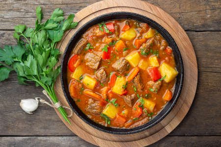 Goulash, beef stew or bogrash soup with meat, vegetables and spices in cast iron pan on wooden table. Hungarian cuisine. Rustic style. Top view. Reklamní fotografie