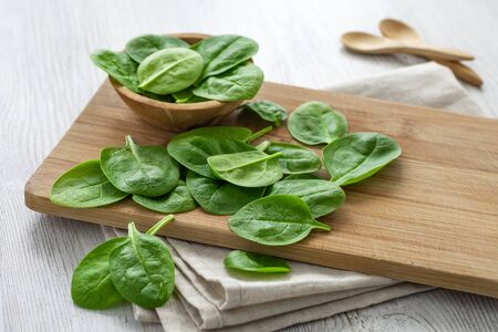 Organic and healthy food. Fresh spinach leaves on wooden cutting board. Reklamní fotografie