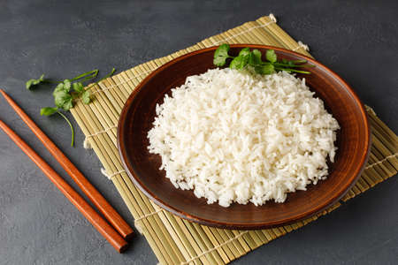 Boiled rice, chopsticks and bamboo napkin on a gray concrete background. Asian food.