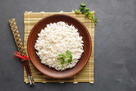 Boiled rice, chopsticks and bamboo napkin on a gray concrete background. Asian food. Top view.