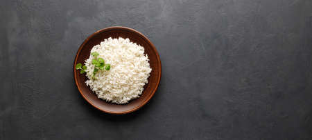 Boiled rice in a brown plate on black concrete background. Asian food. Top view with copy space. Reklamní fotografie