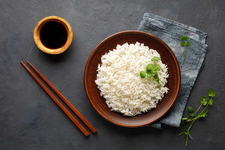 Boiled rice, chopsticks and napkin on a gray concrete background. Asian food. Top view.