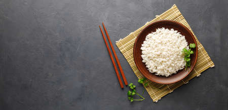Boiled rice, chopsticks and bamboo napkin on a gray concrete background. Asian food. Top view with copy space