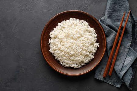 Boiled rice, chopsticks and napkin on a black concrete background. Asian food. Top view. Reklamní fotografie