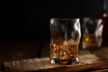 Glass of whiskey with ice on wooden table. Copy space for text.