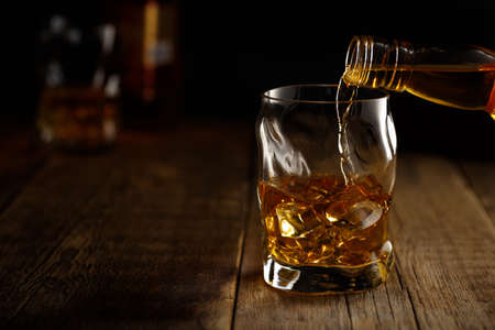 Pouring whiskey drink into a glass with ice. Reklamní fotografie