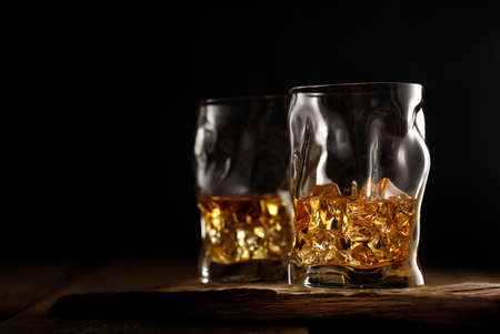 Two glass of whiskey with ice on wooden table. Copy space for text.