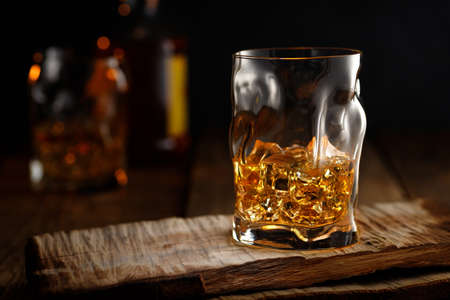 Glass of whiskey with ice on wooden table. Reklamní fotografie