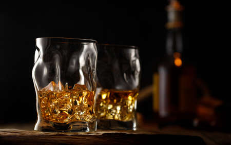 Two glass of whiskey with ice on wooden table.