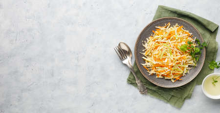 Fresh coleslaw salad from shredded cabbage and carrot on white background. Top view with copy space. Reklamní fotografie