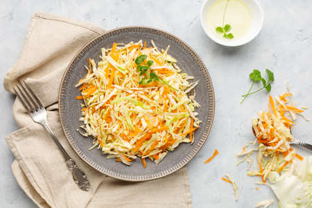 Fresh coleslaw salad from shredded cabbage and carrot on white background. Top view. Reklamní fotografie