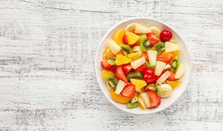 Summer fruit salad in a plate of chopped strawberries, kiwi, banana, orange and cherry on white wooden background. Top view with copy space. Healthy organic food. 免版税图像