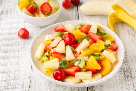 Fruit salad in a plate of chopped strawberries, kiwi, banana, orange and cherry on white wooden background. Healthy organic food.