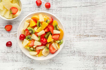 Fruit salad in a plate of chopped strawberries, kiwi, banana, orange and cherry on white wooden background. Top view with copy space. Healthy organic food.