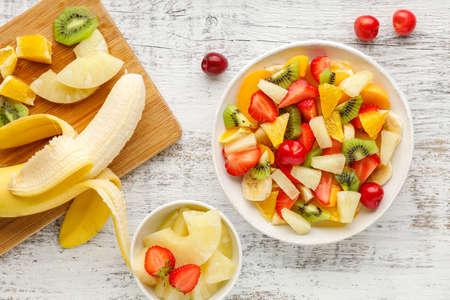 Fruit salad in a plate of chopped strawberries, kiwi, banana, orange and cherry on white wooden background. Top view. Healthy organic food. Reklamní fotografie