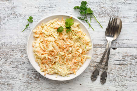 Fresh coleslaw salad from shredded cabbage, carrot and mayonnaise on white wooden table. Top view. Reklamní fotografie
