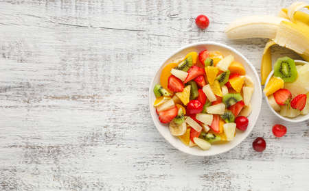 Summer fruit salad in a plate of chopped strawberries, kiwi, banana, orange and cherry on white wooden background. Top view with copy space. Healthy organic food. Reklamní fotografie