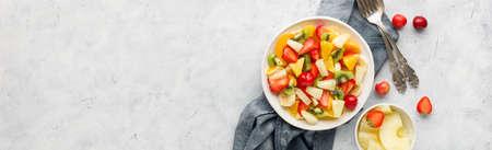 Fresh chopped fruit salad in a bowl. Long banner format.