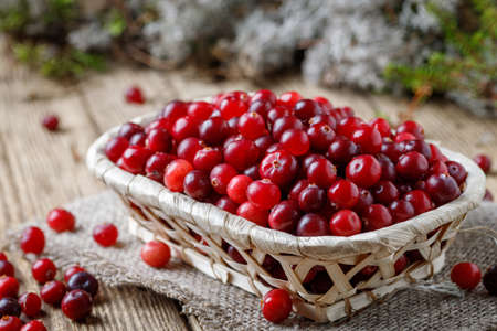 Basket with cranberries on a wooden table 写真素材