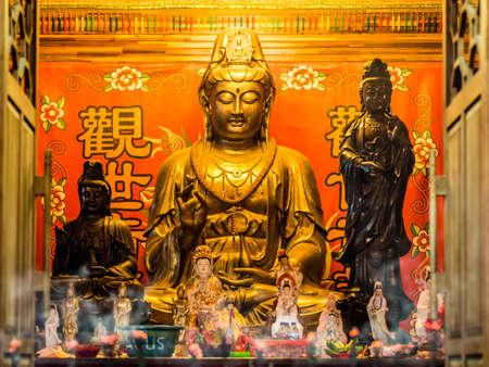 buddhism prayer belief: Guan Yin Goddess Golden Statue Stock Photo