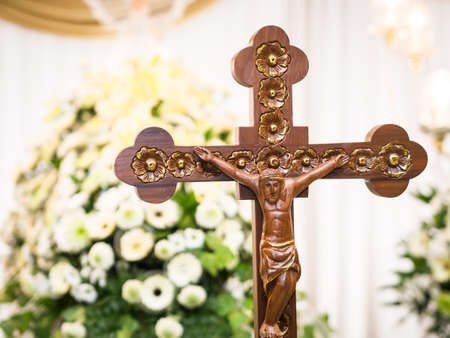 male likeness: Wooden Jesus Christ on Cross with Flower Background