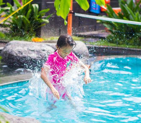 Asian Girl Jump into Swimming Pool Stock Photo