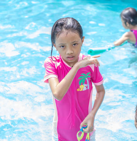 Portrait of Guilty Asian Girl (Kid) at Swimming Pool Stock Photo
