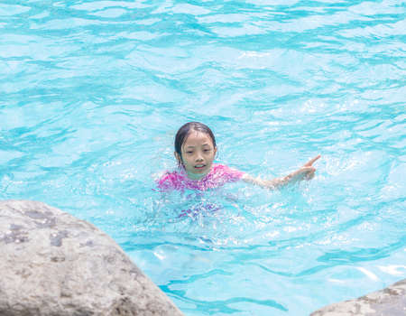 Asian Kid (Girl) in Swimming Pool with Finger Pointing Stock Photo