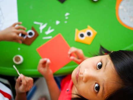 Asian Kid Playing with  Origami Paper Stock Photo