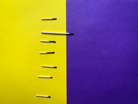 Abstract concept with burnt matches on a half yellow and half purple background layout 免版税图像