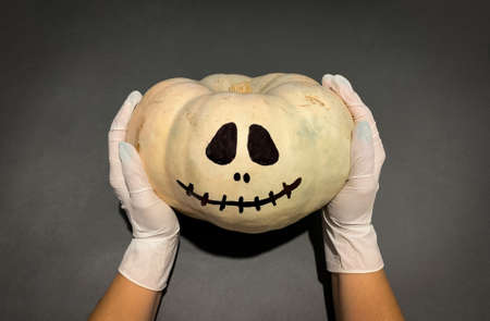 Halloween in Coronavirus pandemic. Hands wearing medical gloves holding jack o lantern white pumpkin 免版税图像
