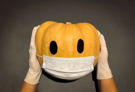 Concept of new normal Halloween showing pumpkin wearing face mask for corona virus protection