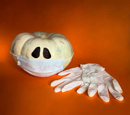 New normal concept Halloween in COVID-19 pandemic. Pumpkin wearing protective mask and medical gloves next to it on a orange background