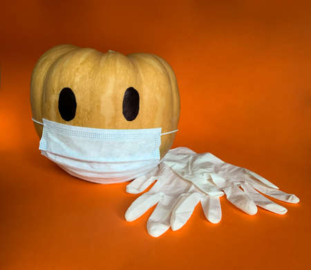 Halloween pumpkin in COVID-19 pandemic wearing protective mask and medical gloves next to it Banque d'images