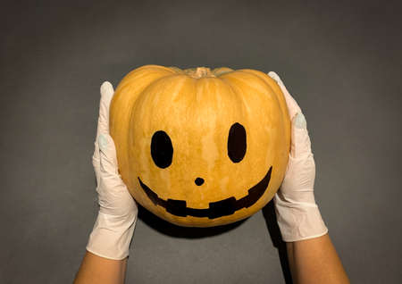 Hands with medical gloves holding Halloween pumpkin head jack lantern. Top view on black background